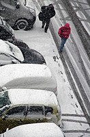 snowed street, people walking in heavy snowfall next to cars covered with snow, winter in Geneve, Switzerland
