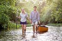 A young man and young woman canoe on a river.