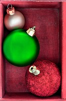 Three green, red and gold Christmas baubles close up in a red wooden box