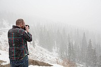 A Man Takes A Picture Of A Landscape In The Falling Snow, Colorado United States Of America