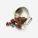Grapes spilling out of a colander