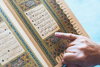 A man reading from the koran with his finger pointing to the text, turkey