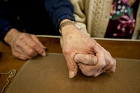 Close up of an elderly couple holding hands.