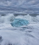 Waves from the atlantic ocean crash into ice calf from breioamerkurjokull a glacial tongue of the vatnajokull ice cap, iceland