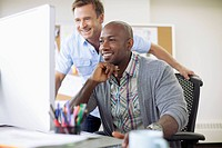 Coworkers looking at job on computer together