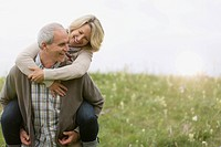 Middle-aged man giving wife a piggy-back ride in meadow (thumbnail)