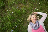 Pretty, middle_aged woman lying in wildflower meadow