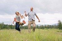 Grandparents having fun with grandson in meadow (thumbnail)