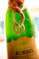 wedding rings tied in a knot around a bottle of korbel champagne