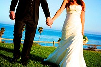 bride & groom excitedly holding hands on way to reception @ gorgeous ocean resort on a sunny beach day