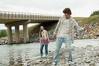 Young couple skipping rocks by stream
