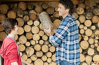 Father and son stacking logs on woodpile