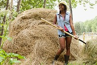 Young adult woman using pitchfork on hay bale