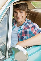 Attractive young man looking out car window