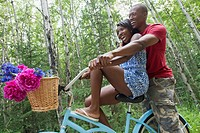 African_American couple having fun riding a bicycle together