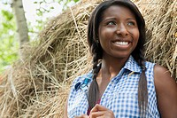 Pretty, African_American woman standing by hay bale