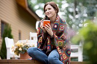 Mid-adult woman warming up outside with coffee and afghan (thumbnail)