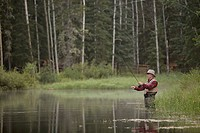 Middle_aged man fly fishing on rural property