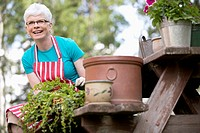 Middle-aged woman repotting plants outdoors (thumbnail)