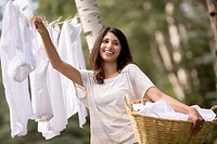 Pretty, mid_adult woman hanging clothes outdoors