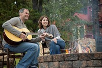 Middle_aged man playing guitar for wife by outdoor fire.