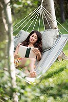 Pretty woman lying in hammock reading (thumbnail)