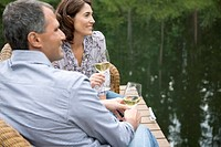 Couple relaxing with wine by the waterfront