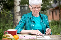 Middle_aged woman playing cards outdoors