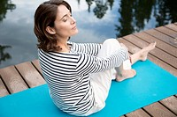 Middle_aged woman meditating on yoga mat outdoors