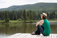 Stylish, mid-adult woman relaxing by the water (thumbnail)
