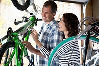 Couple inspecting bicycles together