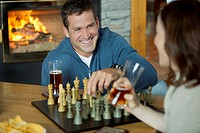Mid_adult couple having fun playing chess together