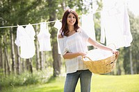 Mid_adult woman with basket of laundry to hang outside
