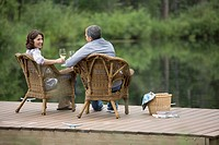 View from behind of middle_aged couple enjoying wine on dock
