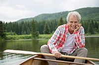 Portrait of smiling, senior man in canoe on the lake