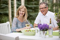 Middle_aged couple enjoying wine with their meal outdoors.