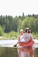 Mature couple rowing in canoe on lake