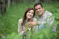 Portrait of mid-adult couple enjoying some wine in the woods (thumbnail)