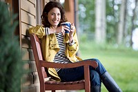 Pretty, middle_aged woman enjoying coffee outside her cottage