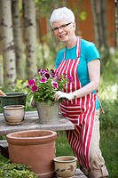 Portrait of middle_aged woman repotting flowers outdoors