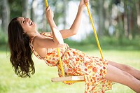 Mid_adult woman laughing on outdoor swing