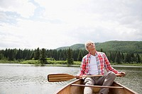 Senior man relaxing with eyes closed in canoe