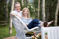 Portrait of middle-aged couple cuddled up on wicker furniture (thumbnail)
