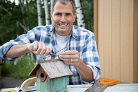 Portrait of middle_aged man repairing birdhouse
