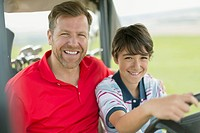 Father and pre_teen son on golf cart together