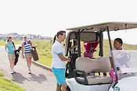 Foursome of female golfers with golf cart.
