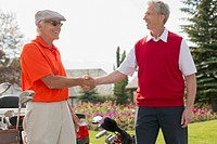 Senior man and middle_aged man shaking hands after golfing