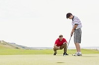 Father coaching son on putting green