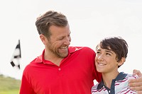 Dad with arm around pre_teen son on golf course