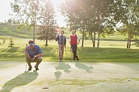 Golfer focused on putt while friends watch
